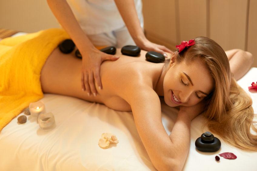 Attraktive Frau bekommt eine Hot Stone Massage - beliebtesten von Wellnessmassagen