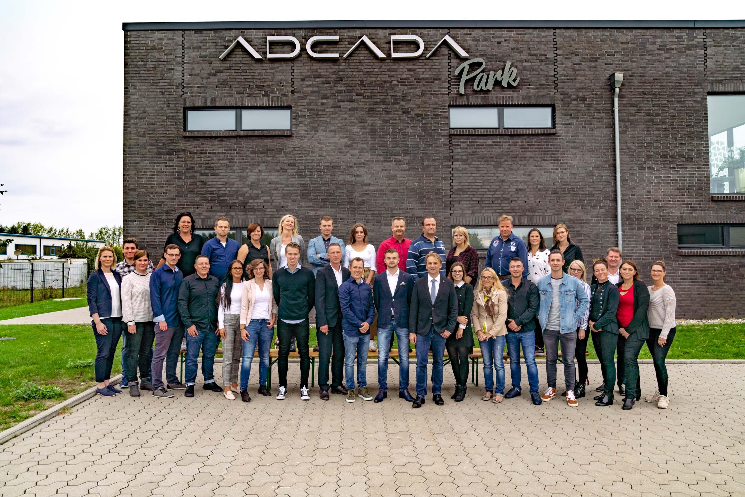 Das ADCADA Team vor dem ADCADA Park-Schriftzug