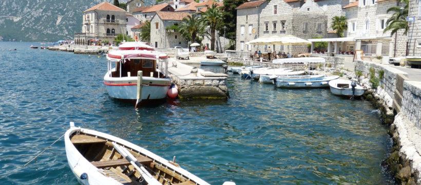 Bucht von Kotor, Fischerboote, blaues Wasser, weiße Steinhäuser, Berge am Ufer, blauer Himmer
