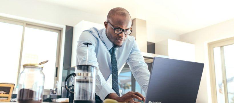 Geschäftsmann mit einem Laptop auf dem Küchentisch zu Hause. Mann arbeitet, während er frühstückt.